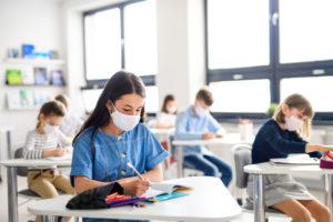 school children sitting at desks with masks.
